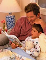 Picture of father listening to his son read a book at bedtime